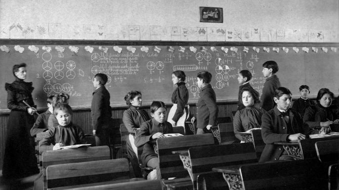 Native Amercian students study at their desks and line up at the chalkboard during class at the Carlisle Indian School in Carlisle, Pennyslvania. (Credit: Library of Congress/Corbis/VCG via Getty Images)