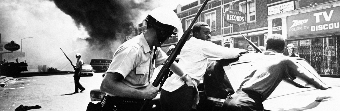A policeman searches black suspects in a Detroit street as buildings are burning during riots that erupted in Detroit following a police operation, 1967. (Credit: AFP/Getty Images)