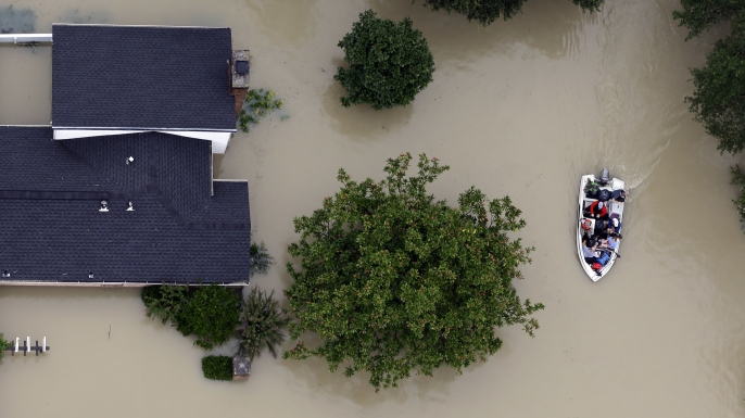 Residents evacuate their homes near the Addicks Reservoir as floodwaters from Hurricane Harvey rise in Houston. (Credit: David J. Phillip/AP Photo)