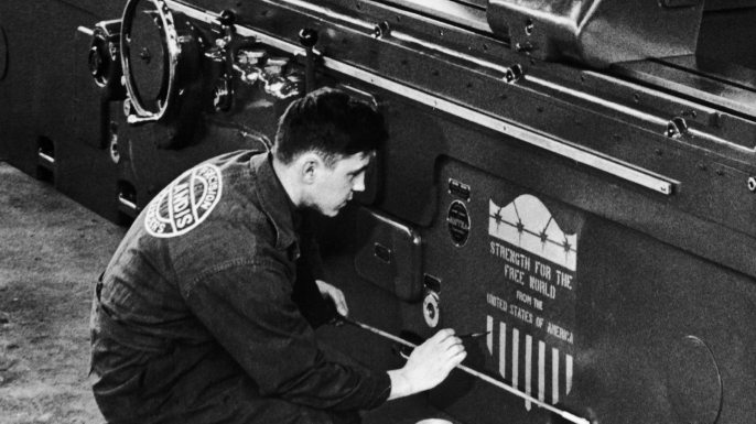 An American worker drawing the new logo of the Marshall Plan on a machine-tool ready to be exported to Europe. (Credit: Keystone-France/Gamma-Keystone via Getty Images)
