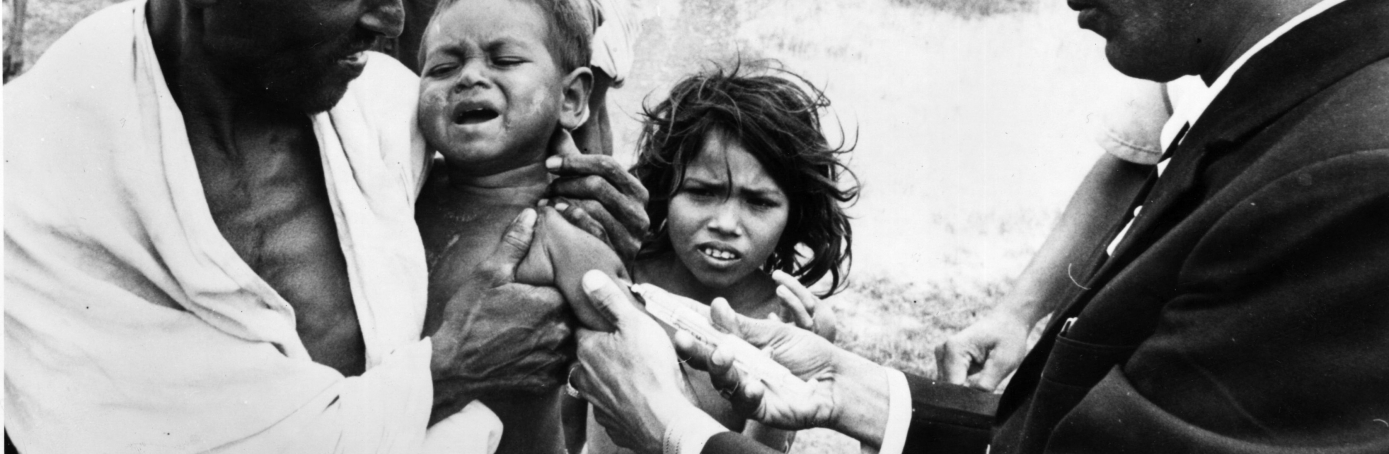 A doctor administering a cholera vaccination to a child at the Indian village of Tarapada, after a cyclone caused havoc in the region, 1971. (Credit:Central Press/Getty Images)