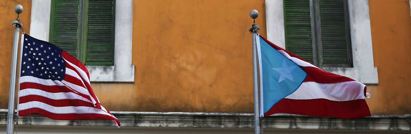 An American flag and Puerto Rican flag fly next to each other in Old San Juan a day after the Puerto Rican Governor Alejandro Garcia Padilla gave a televised speech regarding the governments $72 billion debt in San Juan, Puerto Rico, 2015.  (Credit: Joe Raedle/Getty Images)