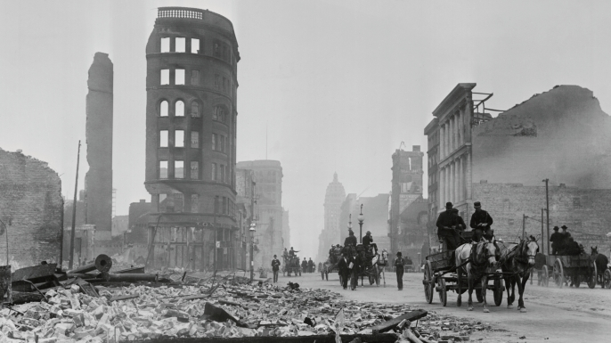 Horse drawn wagons travel past the rubble of stone buildings on Market Street after the 1906 San Francisco earthquake and fire. (Credit: Bettmann/Getty Images)