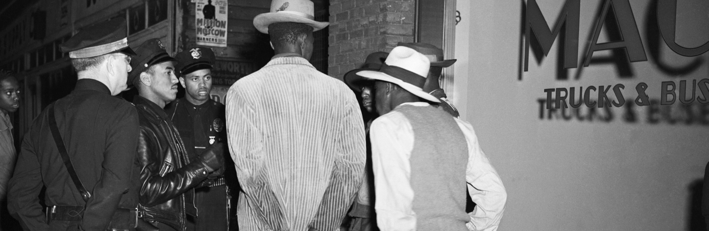 Los Angeles policemen examine draft credentials, as they continue the roundup of zoot-suit suspects in the aftermath of the sixth day of rioting. (Credit: Bettmann/Getty Images)