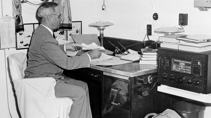August 6, 1945: President Harry S. Truman, with a radio at hand aboard the cruiser USS Augusta, reads reports of the first atomic bomb raid on Japan, while en route home from the Potsdam conference. (Credit: AP Photo)