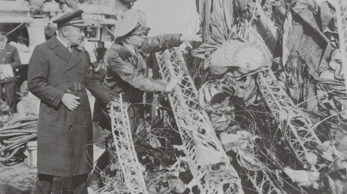 Captain R.A. White, (left) in charge of salvage operations, and Lieut. Commander J.L. Fisher, air expert of Lakehurst, N.J., examine the huge mass of wreckage of the U.S. dirigible Akron, after it had been drawn from the ocean by the U.S.S. Falcon salvage ship. (Credit: Bettmann/Getty Images)
