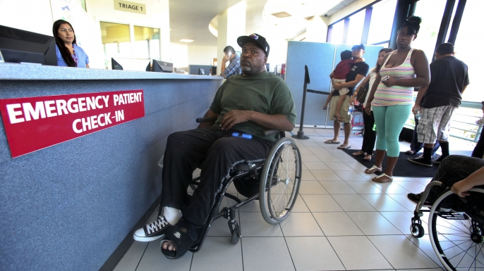 Nikita Hendrix (in wheelchair) waits to be treated for a pressure sore on his foot, during a visit to the emergency room at Long Beach Memorial Hospital, 2014.  In one of the first signs of the effects of Obamacare, most hospitals in Los Angeles County had an increase in visits to their emergency departments in the first part of 2014. (Credit: Mel Melcon/Los Angeles Times via Getty Images)