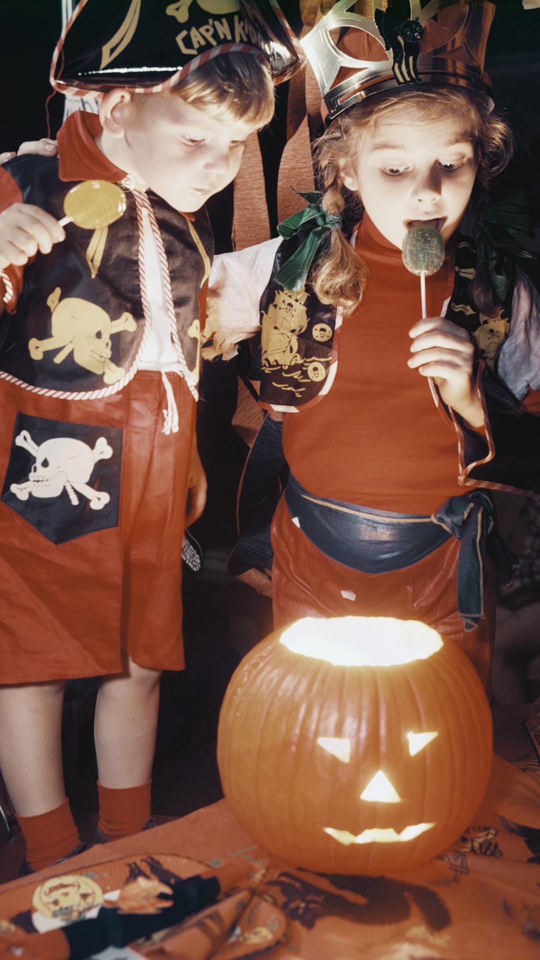 Children looking into glowing jack-o-lantern