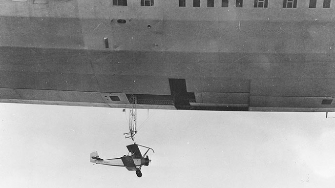 USS Akron launching a Consolidated N2Y-1 training plane during flight tests near Naval Air Station Lakehurst, New Jersey, 1932. (Credit: U.S. Navy Naval History and Heritage Command)