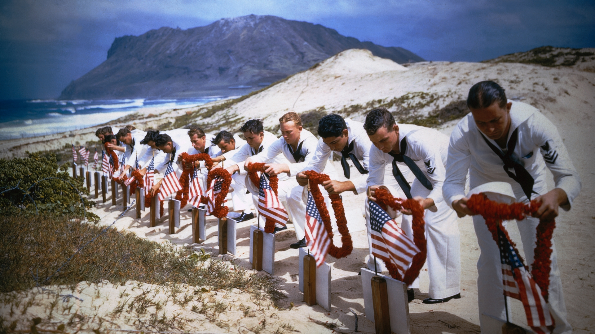 Enlisted men of the Naval Air Station at Kaneohe, Hawaii, place leis on the graves of their comrades killed in the Japanese attack on Pearl Harbor last December 7th in this 1942 photo. Graves were dug along the shore of the Pacific Ocean. (Credit: Bettmann/Getty Images)