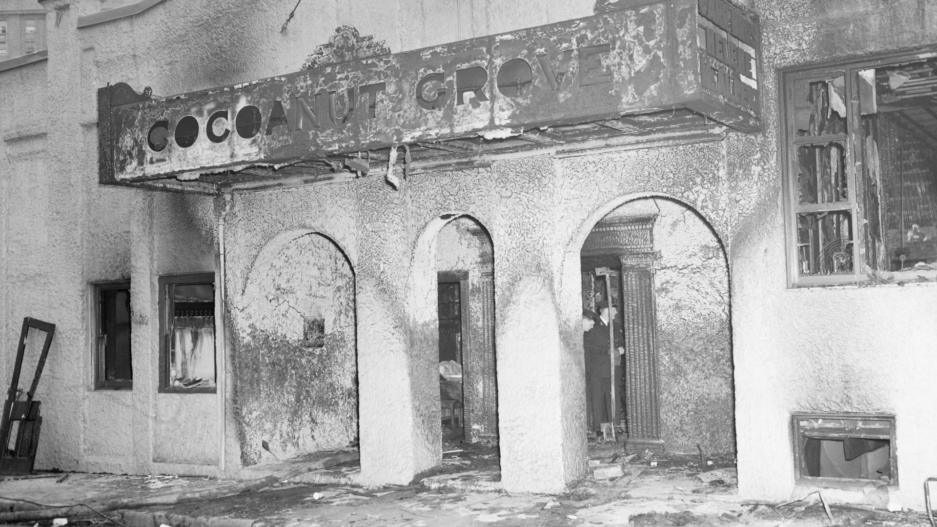 Firemen looking through the remains of Boston's Cocoanut Grove night club through the revolving doors leading to the tiny 10-foot-wide vestibule where stampeding guests were crushed and smothered as they tried to leave the burning club. (Credit: Bettmann Archive/Getty Images)