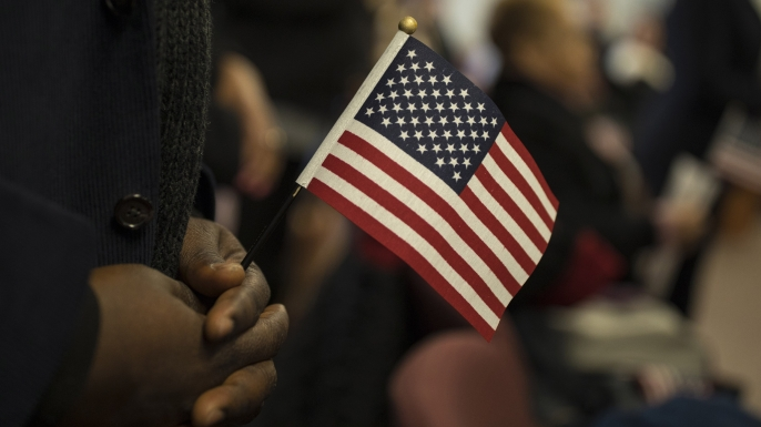 A candidate for US citizenship holds a US flag during a naturalization ceremony for new US citizens in Newark, New Jersey, 2017. (Credit: Robert Nickelsberg/Getty Images)