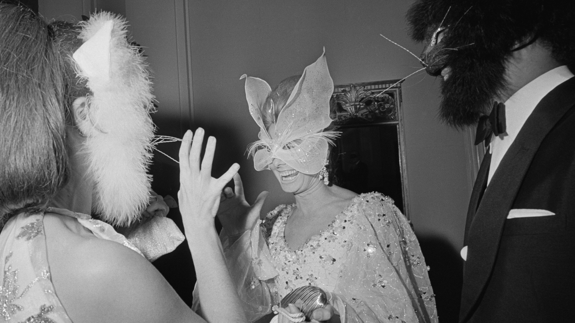 Vogue Editor Francoise Langlade (left) and Oscar de la Renta (right) in cat masks speaking with Anne McDonnell, wife of Henry Ford, in a butterfly mask. (Credit: Harry Benson/Daily Express/Hulton Archive/Getty Images)