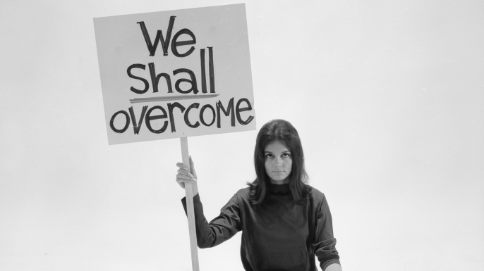 Gloria Steinem sitting cross-legged on floor with sign We Shall Overcome sign. (Credit: Yale Joel/The LIFE Picture Collection/Getty Images)