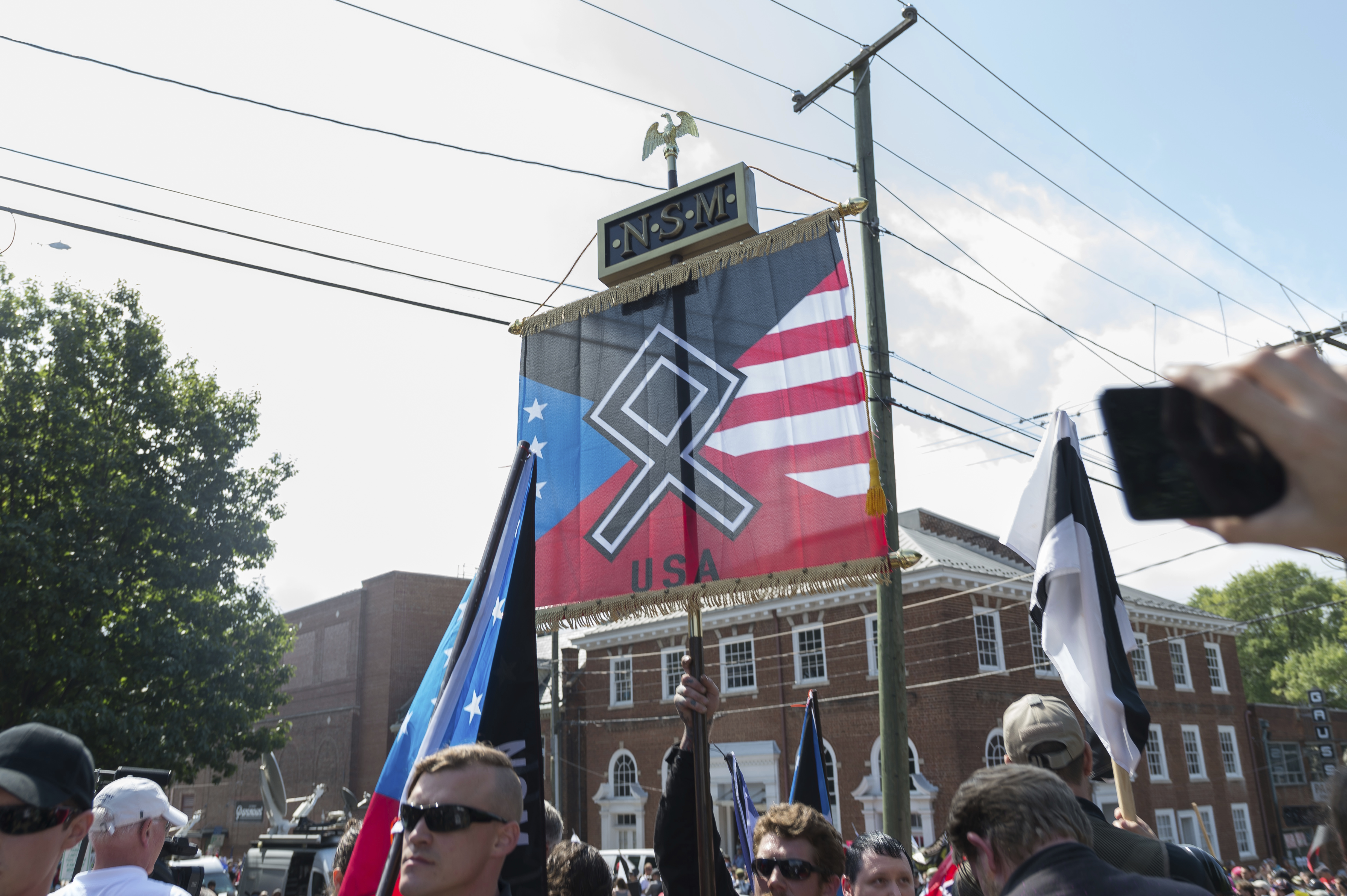 "A man from an alt-right group carrying a flag with the othala rune before Virginia State Police ordered the evacuation by all parties and cancellation of the ""Unite The Right"" rally scheduled to take place in Emancipation Park, Charlottesville, Virginia, 2017. (Credit: Albin Lohr-Jones/Pacific Press) *** Please Use Credit from Credit Field ***(Sipa via AP Images)"