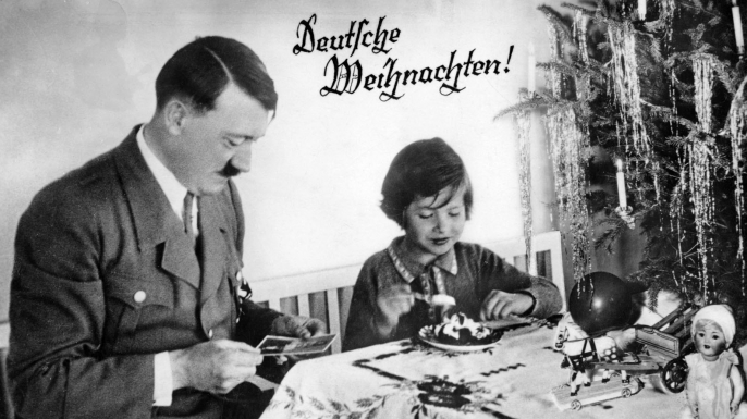 Adolf Hitler with a child on a card that reads 'Deutsche Weihnachten!', meaning 'German Christmas!'. (Credit: Culture Club/Getty Images)