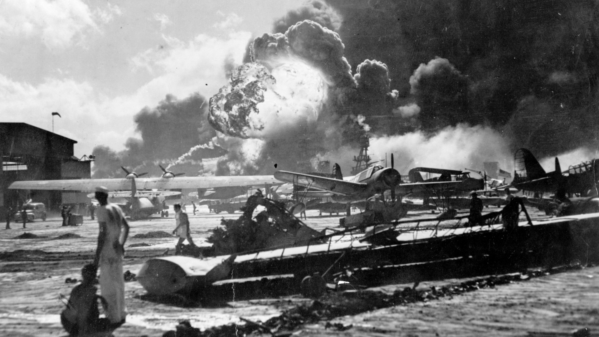 An explosion at the Naval Air Station during the Japanese attack at Pearl Harbor. Sailors stand amid wrecked watching as the USS Shaw explodes in the center background. The USS Nevada is also visible in the middle background, with her bow headed toward the left. (Credit: Fox Photos/Getty Images)