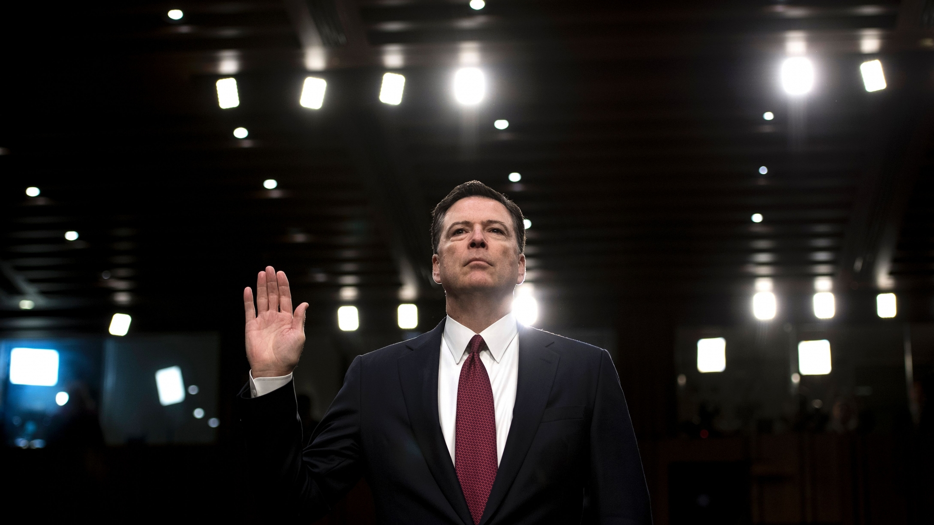 Fired FBI director James Comey being sworn into a crucial Senate hearing, repeating explosive allegations that President Donald Trump badgered him over the highly sensitive investigation Russia's meddling in the 2016 election. (Credit: Brendan Smialowski/AFP/Getty Images)