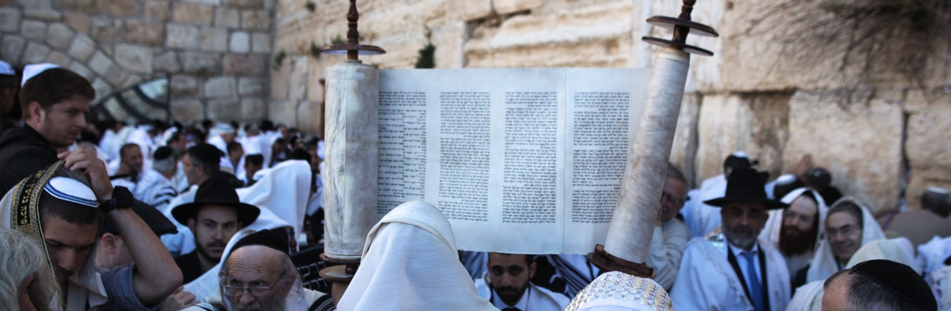 A Jewish man holding up a Torah scroll as they  perform the Cohanim prayer (priest's blessing) during the Pesach (Passover) holiday at the Western Wall in the Old City of Jerusalem, 2015. (Credit: Menahem Kahana/AFP/Getty Images)