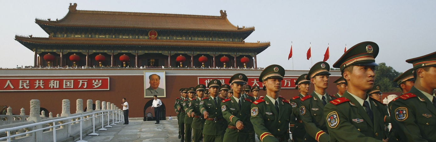 Armed policemen march out of the Tiananmen Gate to prepare for the national flag lowering ceremony at Tiananmen Square in Beijing, China, 2006. Thousands of Chinese gather on Tiananmen Square to mark the 57th anniversary of the founding of People's Republic of China. (Credit: China Photos/Getty Images)