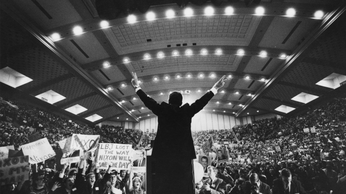 Richard Nixon, then the Republican presidential candidate, standing on stage in front of an arena of supporters giving the victory 'V' sign with both hands, 1968. (Credit: Hulton Archive/Getty Images)