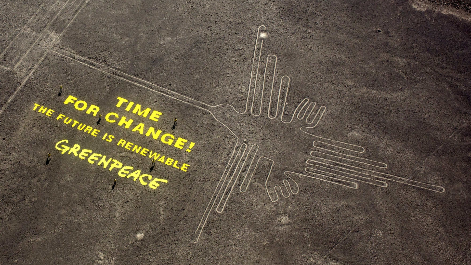 """Greenpeace activists standing next to large letters that spell out """"Time for Change: The Future is Renewable"""" next to the hummingbird geoglyph in Nazca, Peru. (Credit:Rodrigo Abd/AP Photo)"""
