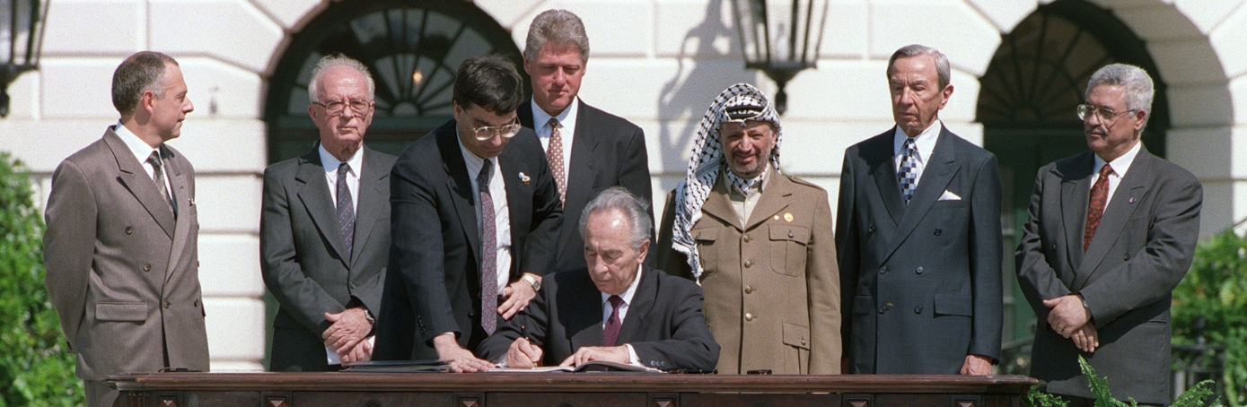 Israeli Foreign Minister Shimon Peres signing the historic Oslo Accords on Palestinian autonomy in the occupied territories on September 13, 1993. (Credit: J. David Ake/AFP/Getty Images)