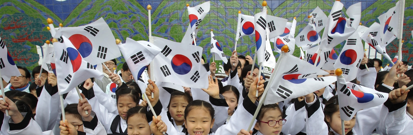 South Korean students wearing traditional costume wave national flags during the celebration of Independence Movement Day in Seoul, South Korea. (Credit: Chung Sung-Jun/Getty Images)