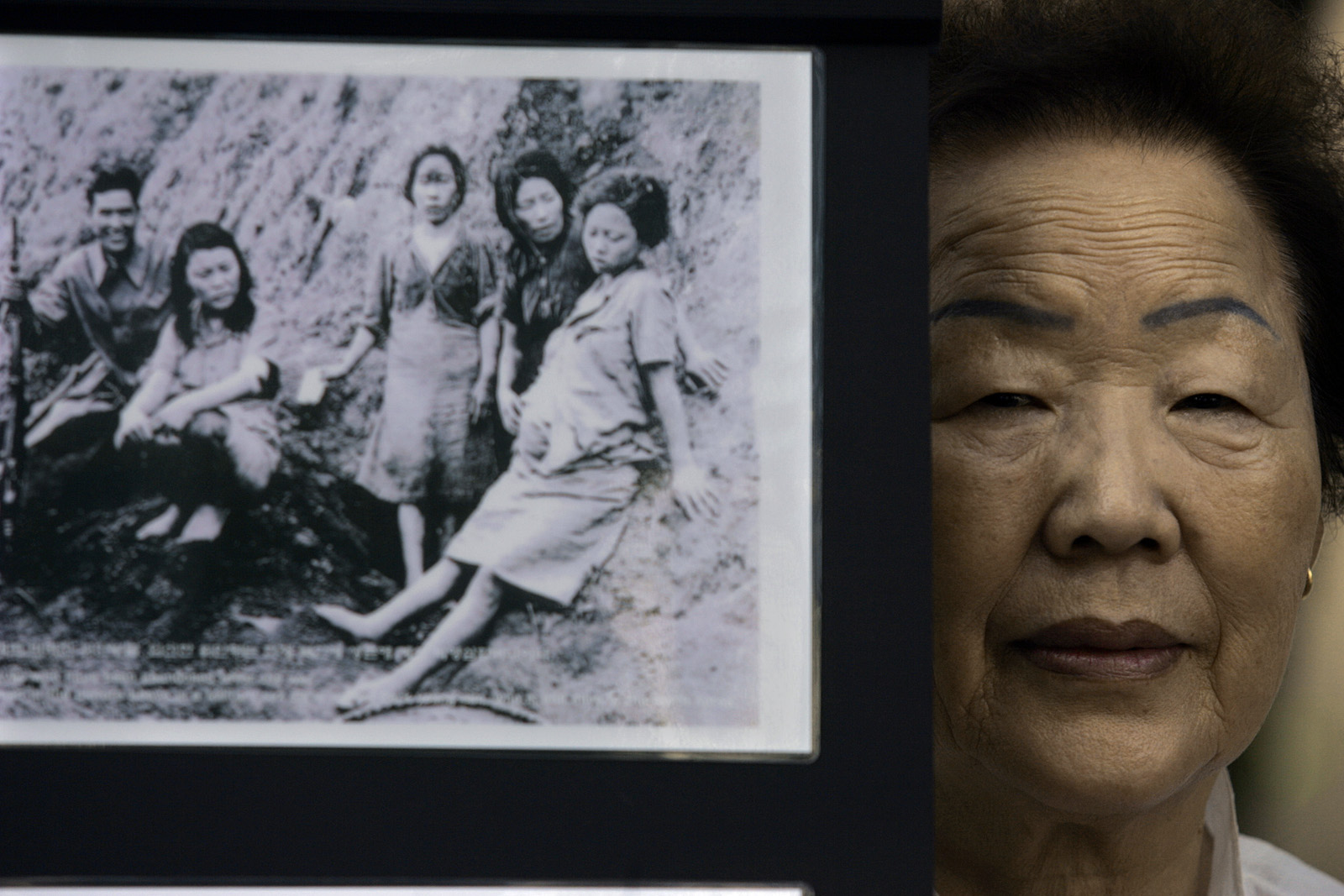 Former comfort woman Yong Soo Lee next to a picture of comfort girls. (Credit: Gary Friedman/Los Angeles Times/Getty Images)