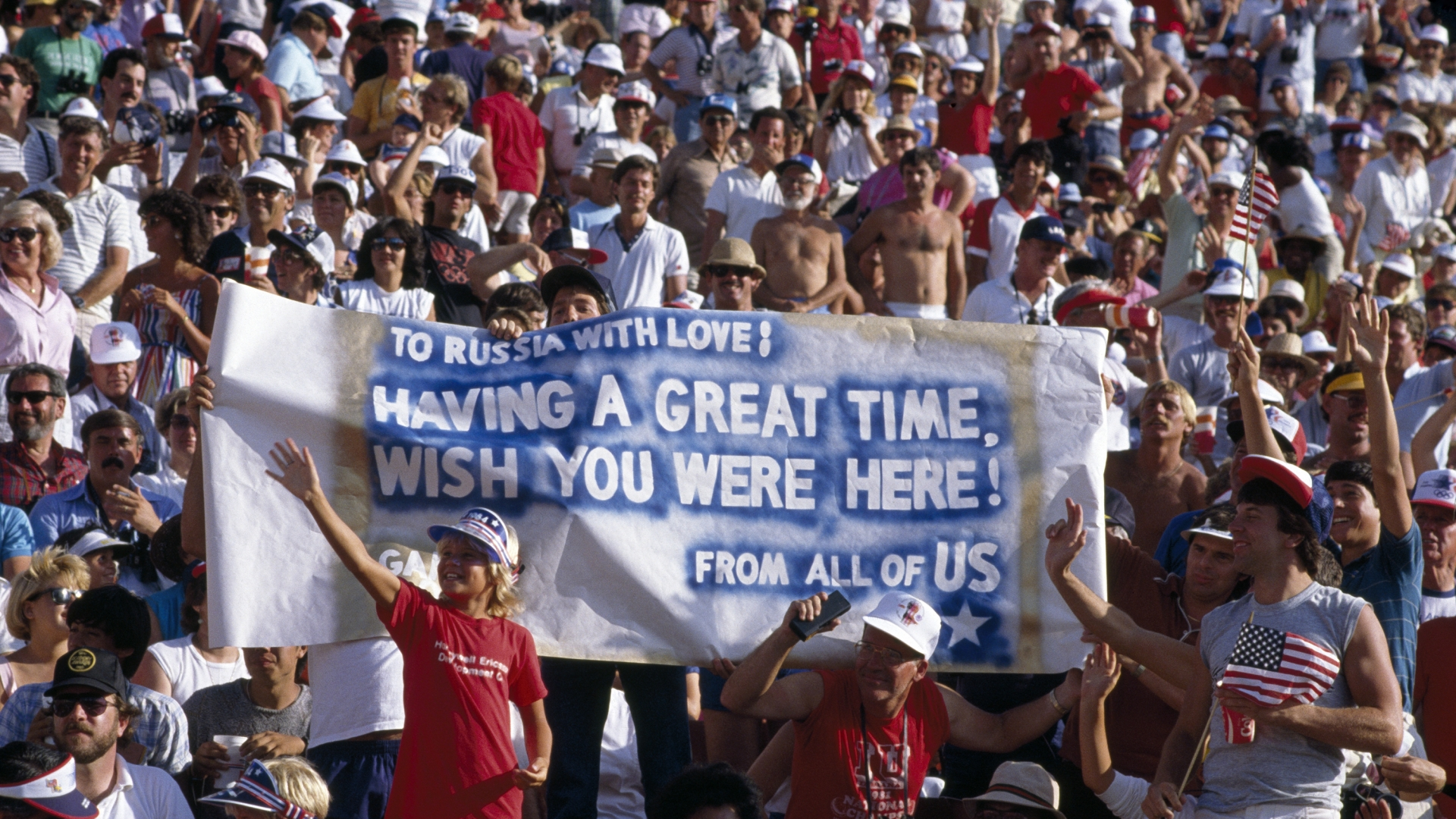 American athletics fans displaying a banner with the message 'To Russia With Love! Having a Great Time, Wish You Were Here', in reference to the boycott of the Games by the Soviet Union. (Credit: Bob Thomas/Getty Images)