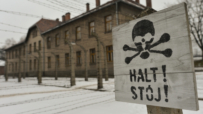A warning sign near the entrance to the former Auschwitz camp. (Credit: Artur Widak/NurPhoto/Getty Images)