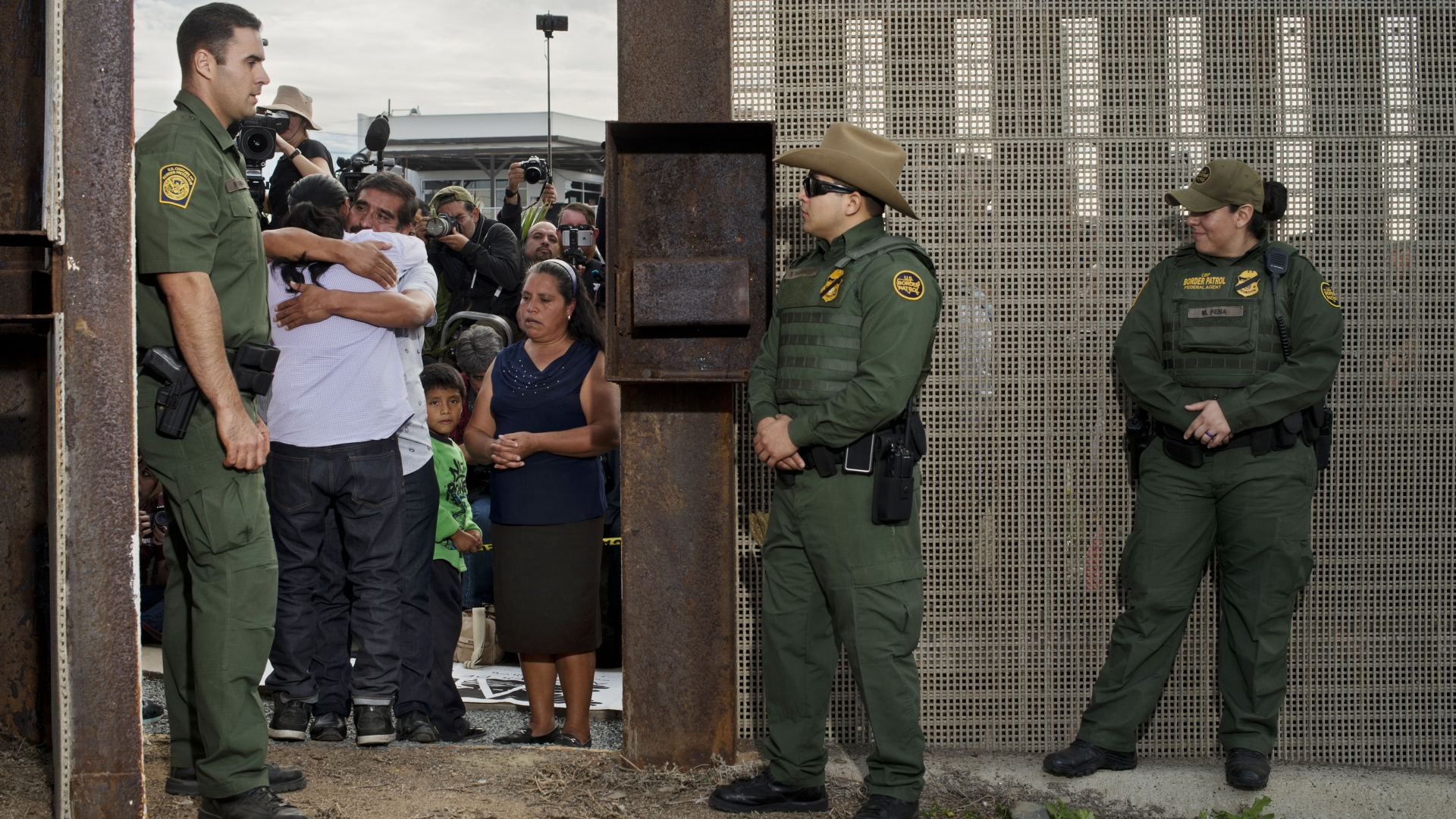 Border-patrol agents guarding the U.S. side of the Mexican border at San Diego open the gate to let six families unite and hug for three minutes each before closing the gate again. The event is organized by Border Angels, a migrant-advocacy group. (Credit: Carolyn Drake/Magnum)