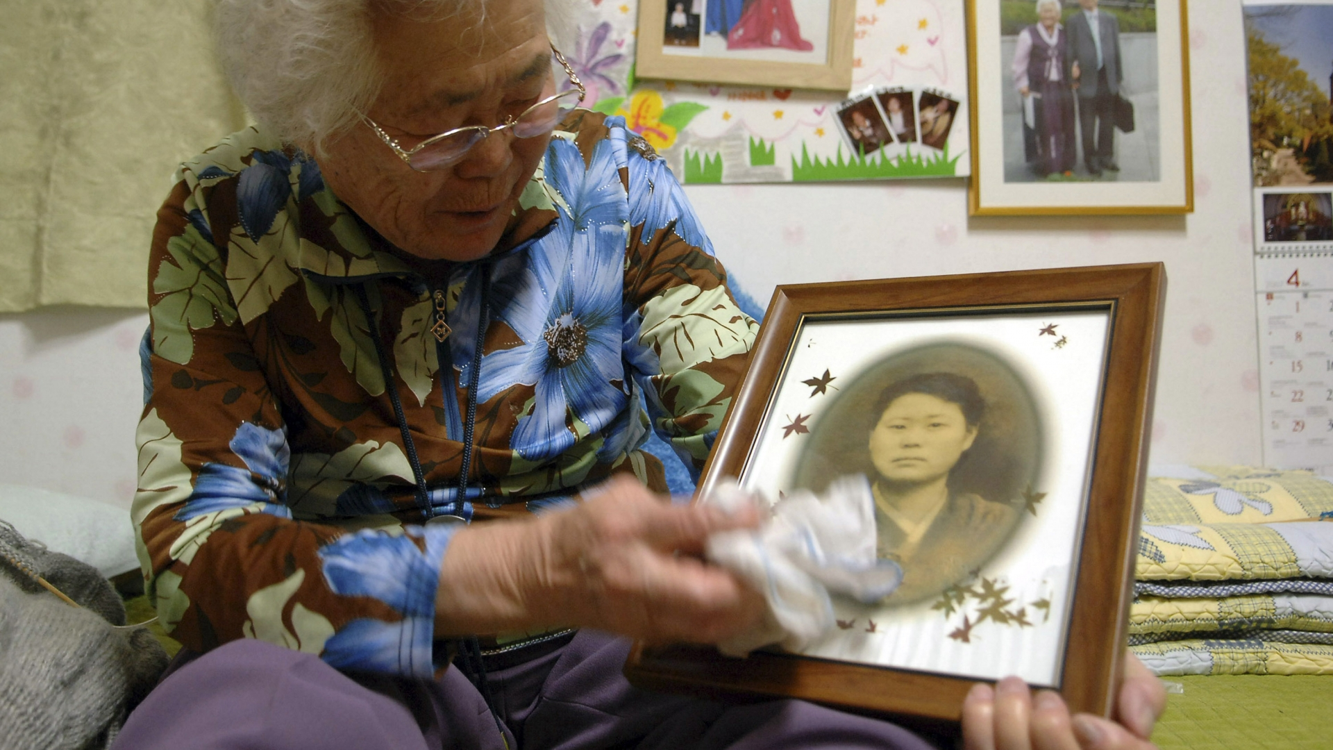 Lee Ok-seon, then 80, in a shelter for former sex slaves near Seoul, South Korea, holding an old photo of herself on April 15, 2007. (Credit: Seokyong Lee/The New York Times/Redux)
