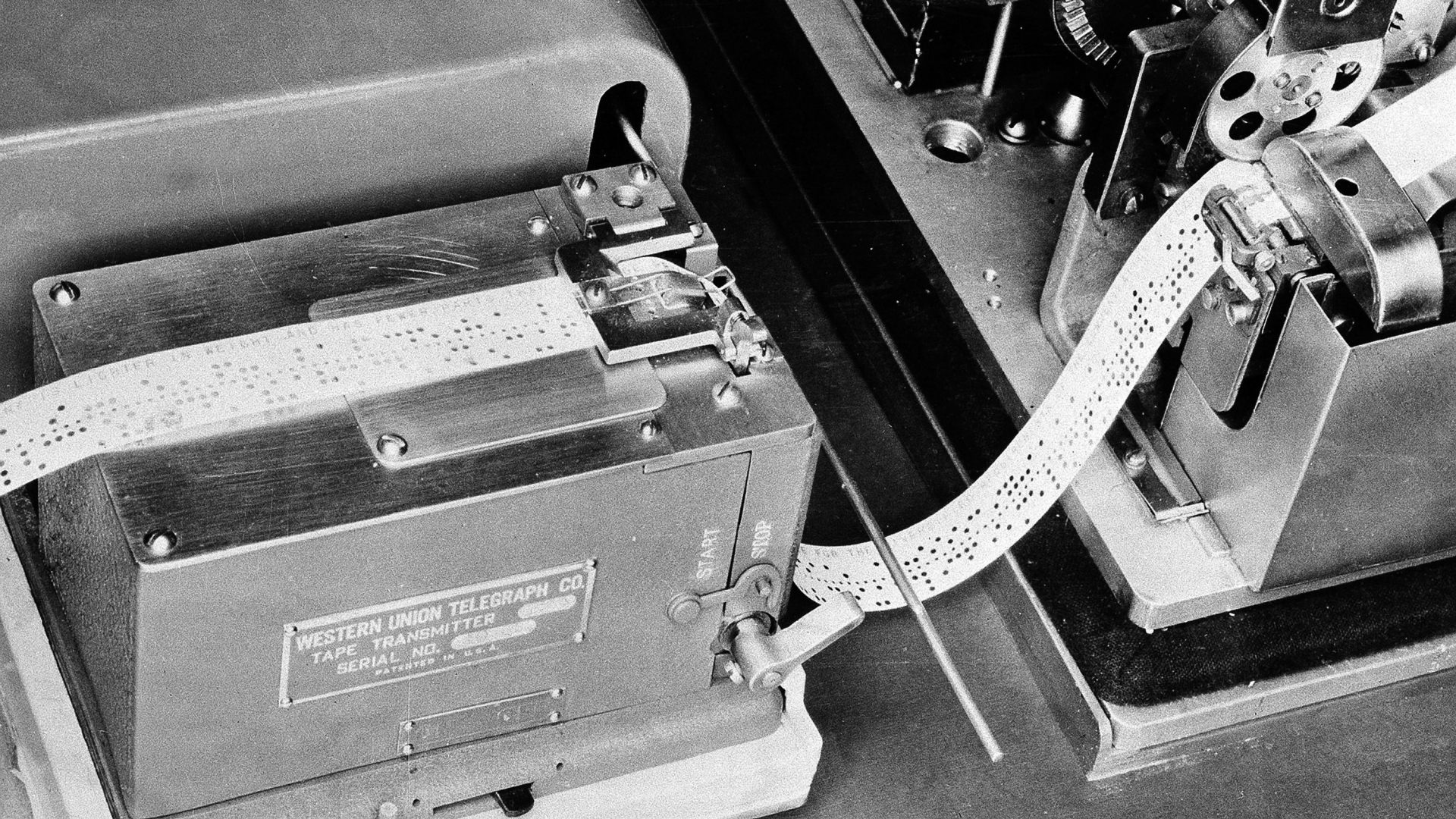 A 1944 photo of the device used by Western Union which translates a telegram into holes on a tape, and then passes it along to the box-like apparatus. (Credit: AP Photo)