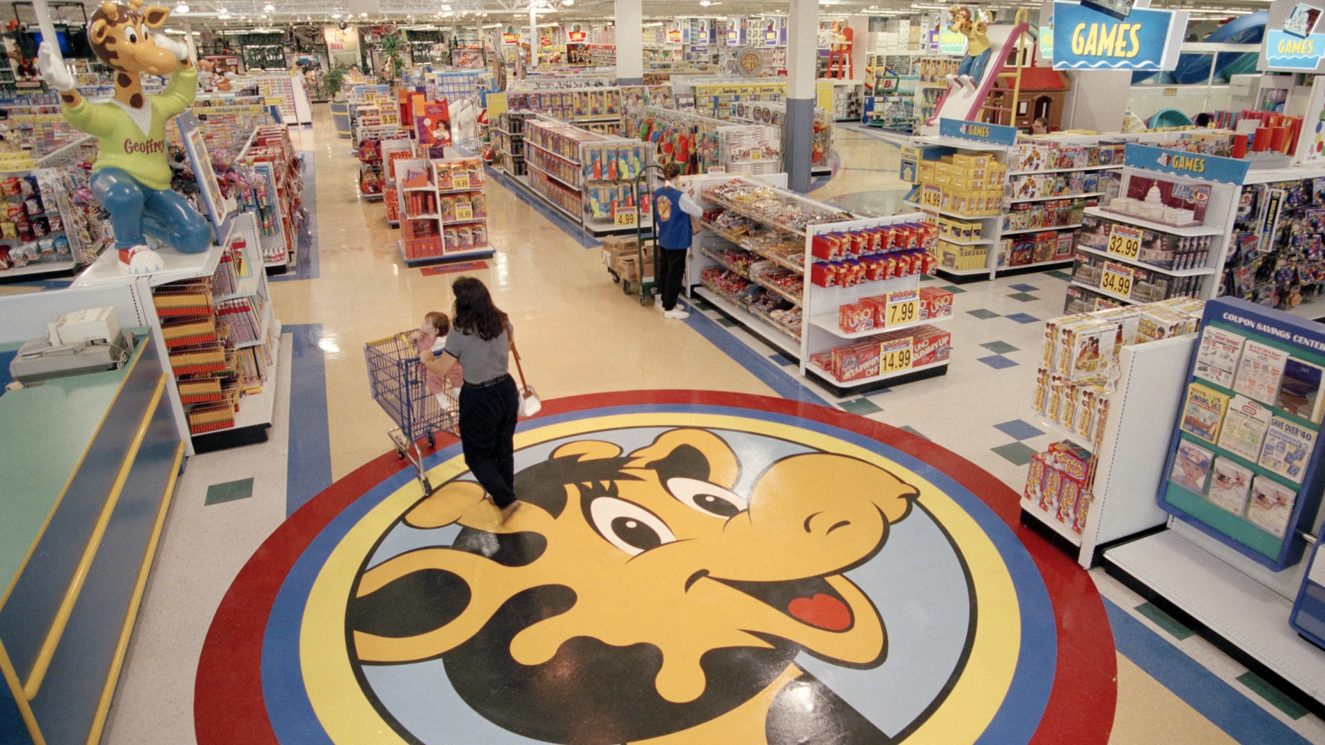 A woman and her child shopping in a New Jersey Toys R Us which features their mascot, Geoffrey the giraffe, 1996. (Credit: Daniel Hulshizer/AP Photo)