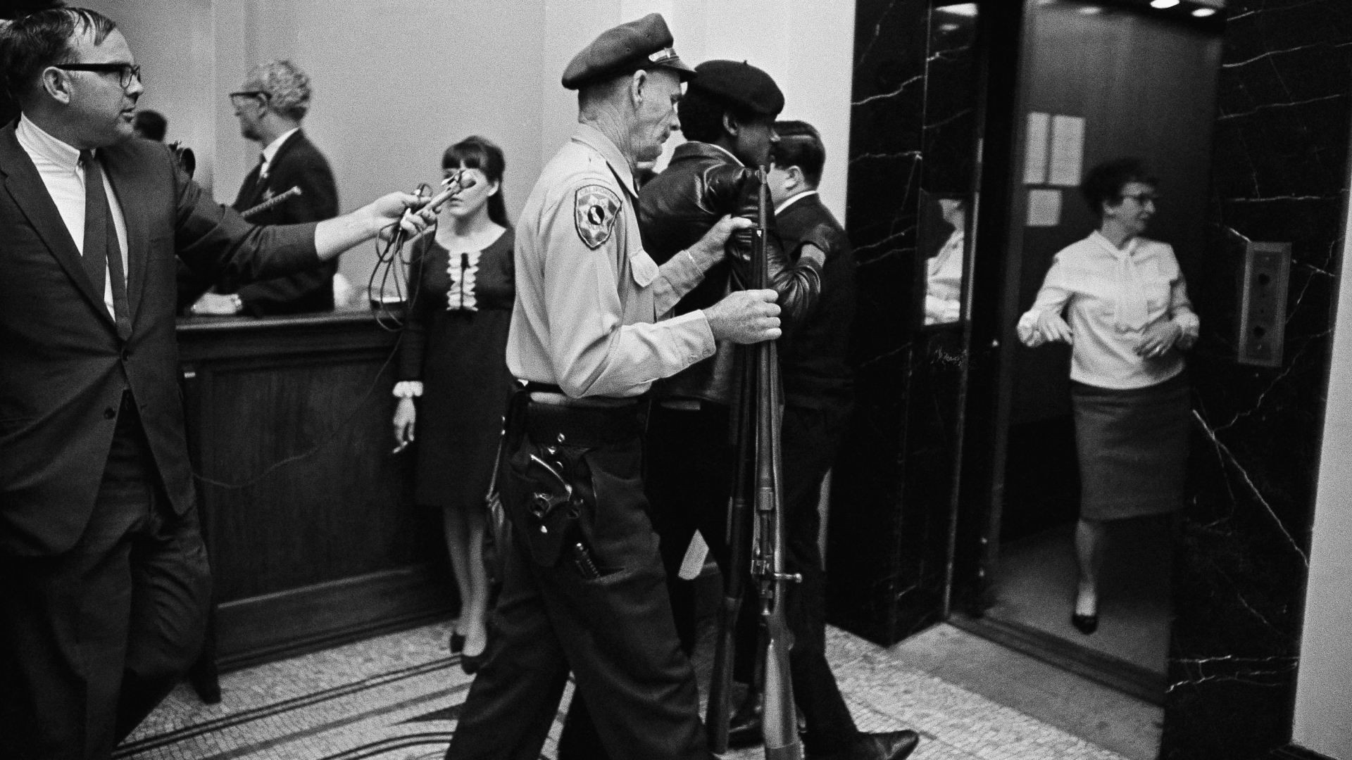 A California State Policeman escorting a member of the Black Panther Party down the corridor of the Capitol in Sacramento, 1967. (Credit: AP Photo )