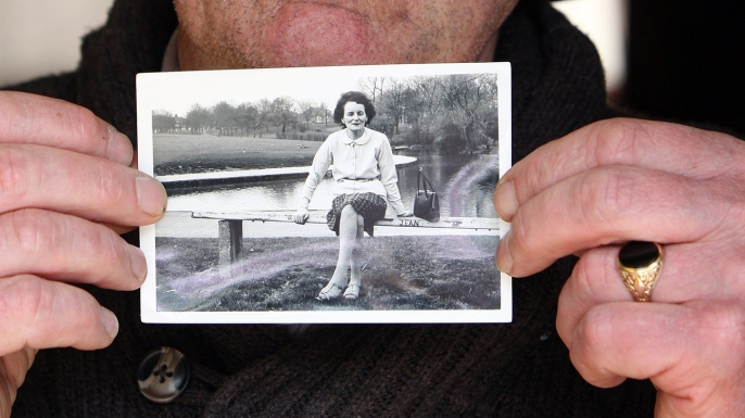 John Pascal Rodgers, who was born in Tuam, Ireland, at a home for unmarried mothers run by nuns, poses with a photograph of his mother Bridie Rodgers. (Credit: Paul FaithAFP/Getty Images)