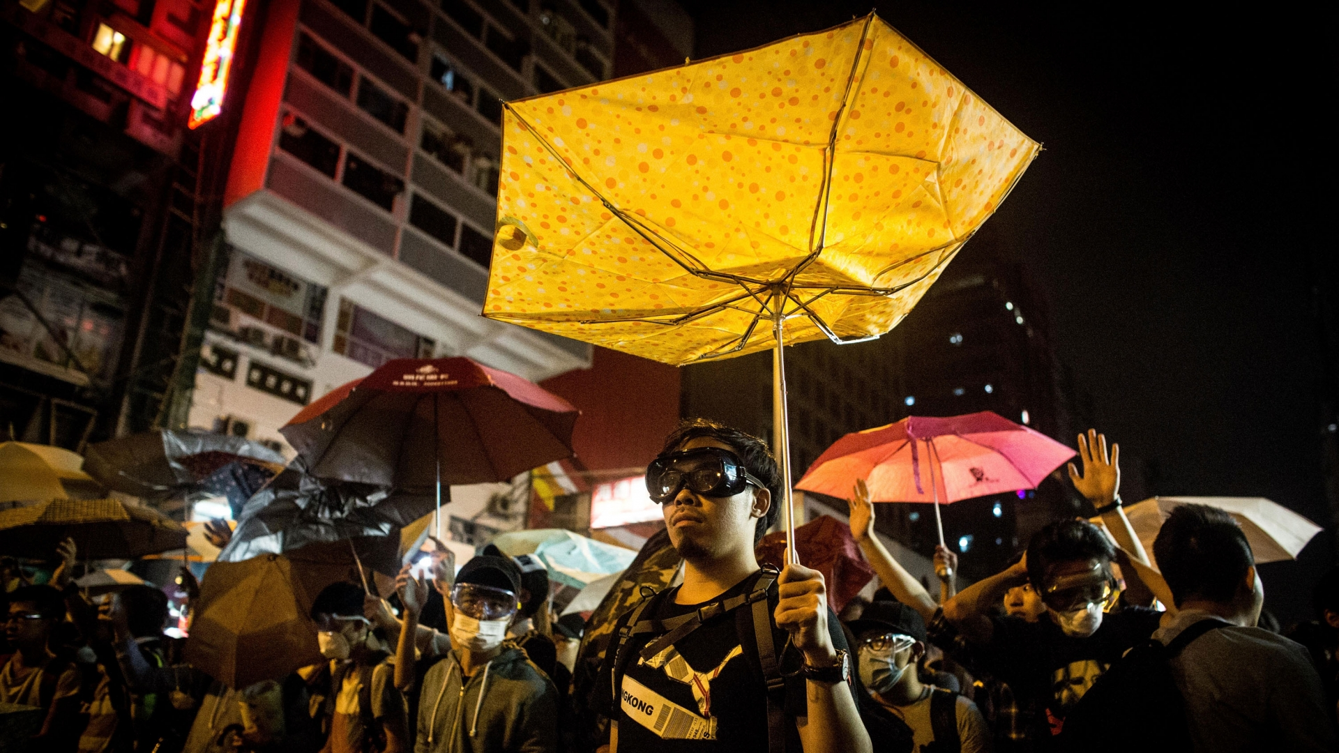 Pro-democracy protesters holding umbrellas in front of police during clashes on a street in Mong Kok on October 19, 2014 in Hong Kong. (Credit: Chris McGrath/Getty Images)