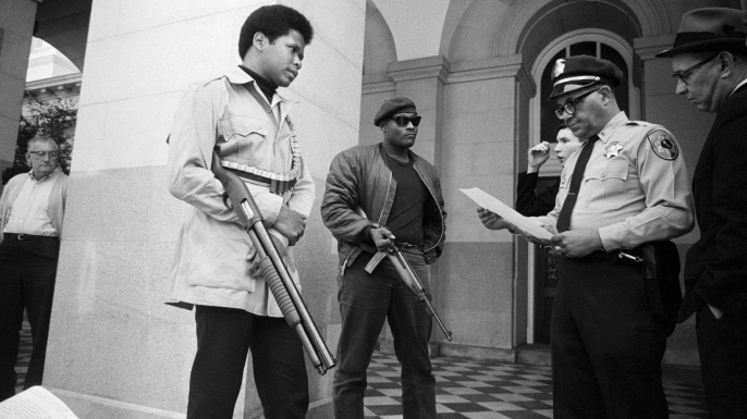 Two members of the Black Panther Party are met on the steps of the State Capitol in Sacramento, May 2, 1967, by Police Lt. Ernest Holloway, who informs them they will be allowed to keep their weapons as long as they cause no trouble and do not disturb the peace. (Credit: Bettmann Archive/Getty Images)