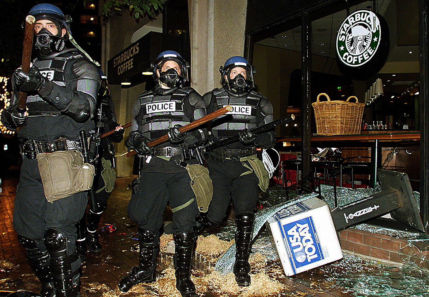 Seattle riot police marching past a damaged Starbucks during demonstrations against the World Trade Organization, 1999. (Credit: Mike Nelson/AFP/Getty Images)
