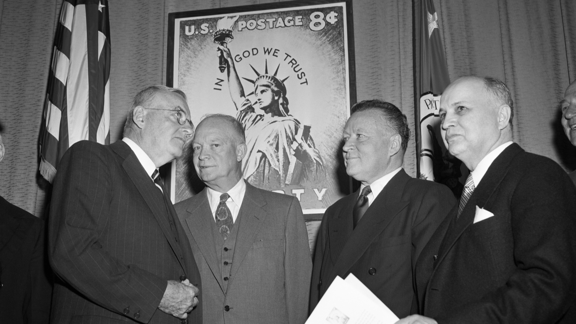 Secretary of State John Foster Dulles, President Eisenhower, Postmaster General Arthur Summerfield and Dr. Roy G. Ross of the National Council of Churches shown at a Post Office Department ceremony introducing the nation's first regular stamp bearing a religious significance with the inscription 'In God We Trust.' (Credit: Bettmann Archives/Getty Images)