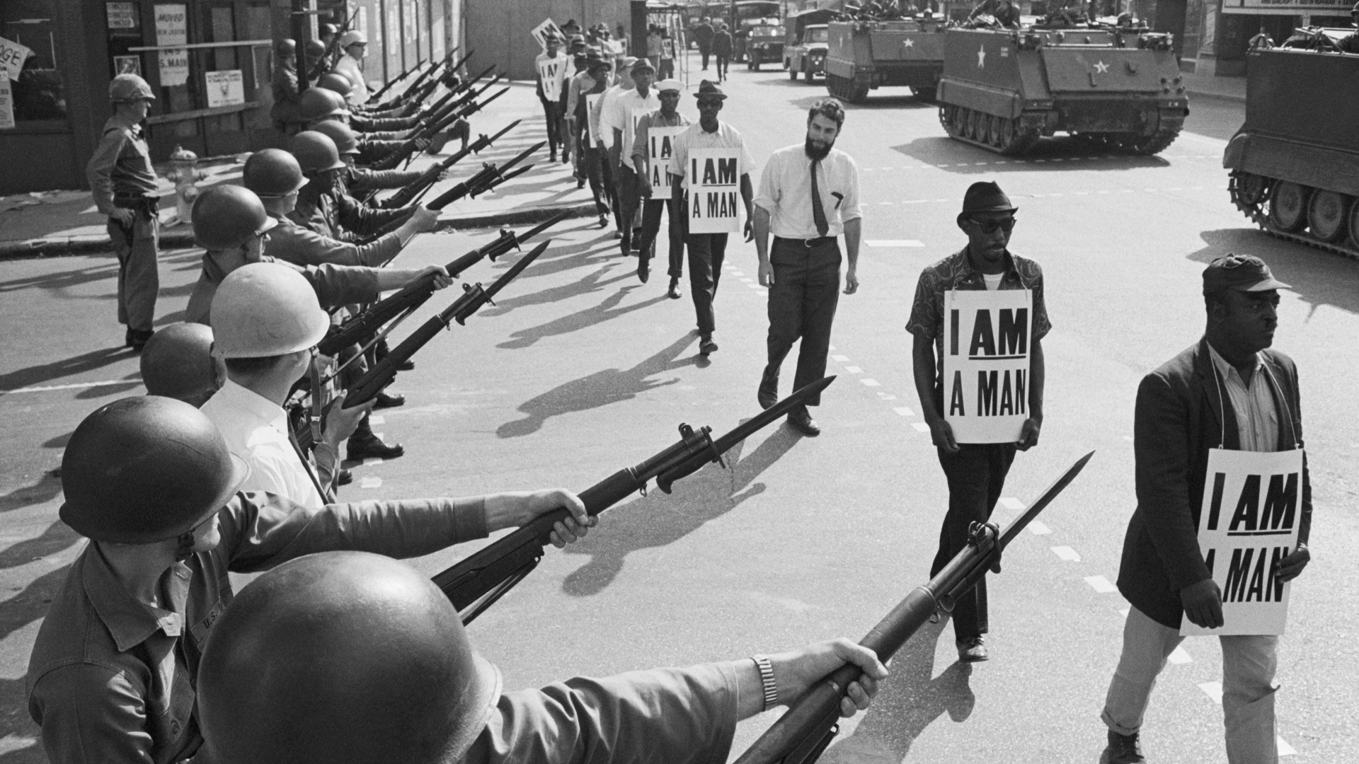U.S. National Guard troops blocking off a street while striking Memphis sanitation workers march by, wearing placards reading, 'I Am A Man' on March 29, 1968. King was killed on the eve of a second march to support the sanitation workers. (Credit: Bettmann Archive/Getty Images)