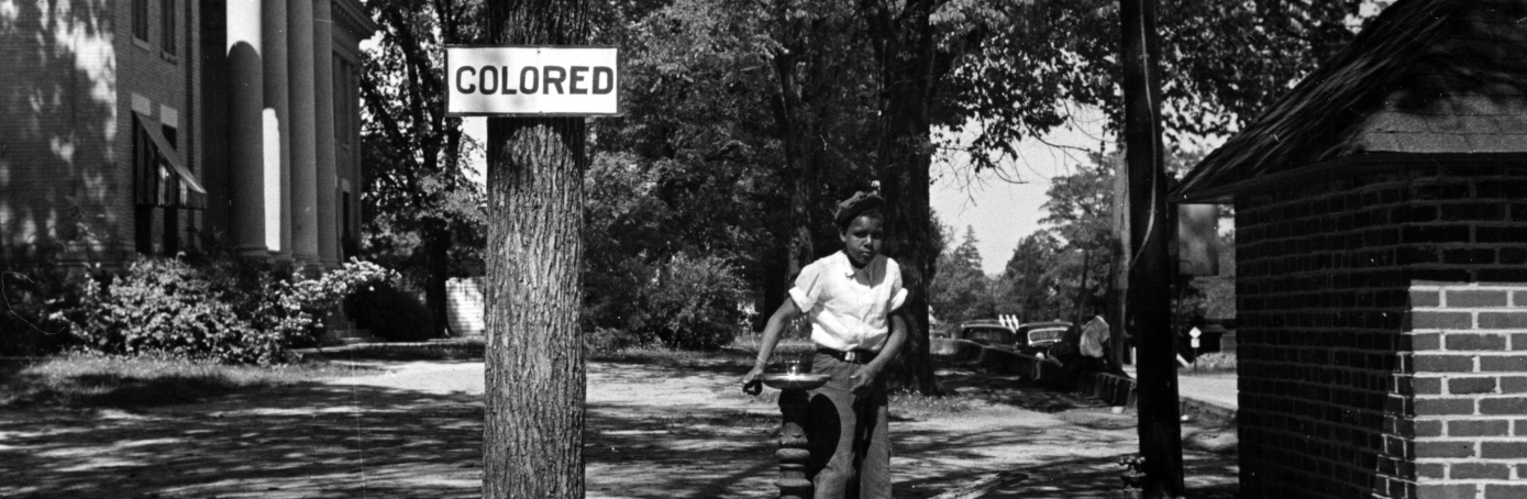 An African American child using a designated water fountain enforced by Jim Crow laws, North Carolina, 1938. (Credit: Smith Collection/Gado/Getty Images)
