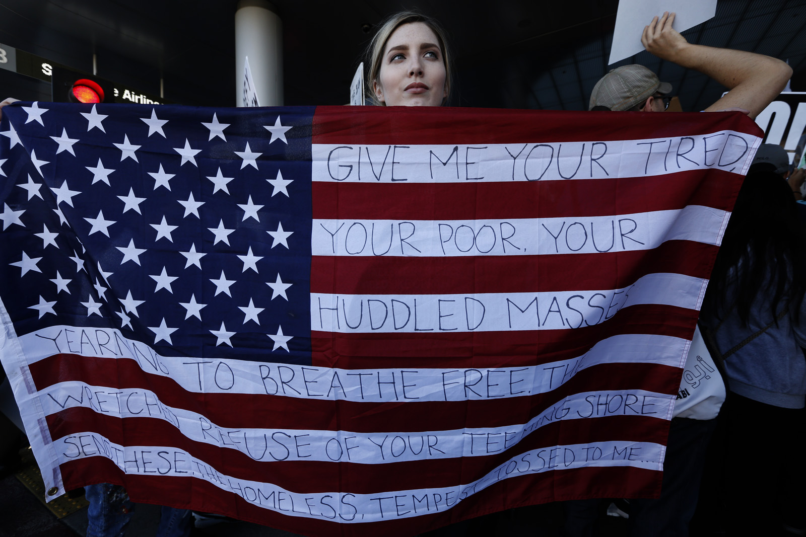 """A woman holding a U.S. flag with words from """"The New Colossus"""" poem that is on the Statue of Liberty, while protesting President Donald Trump's travel ban at the Los Angeles International Airport, 2017. (Credit: Genaro Molina/LA Times via Getty Images)"""