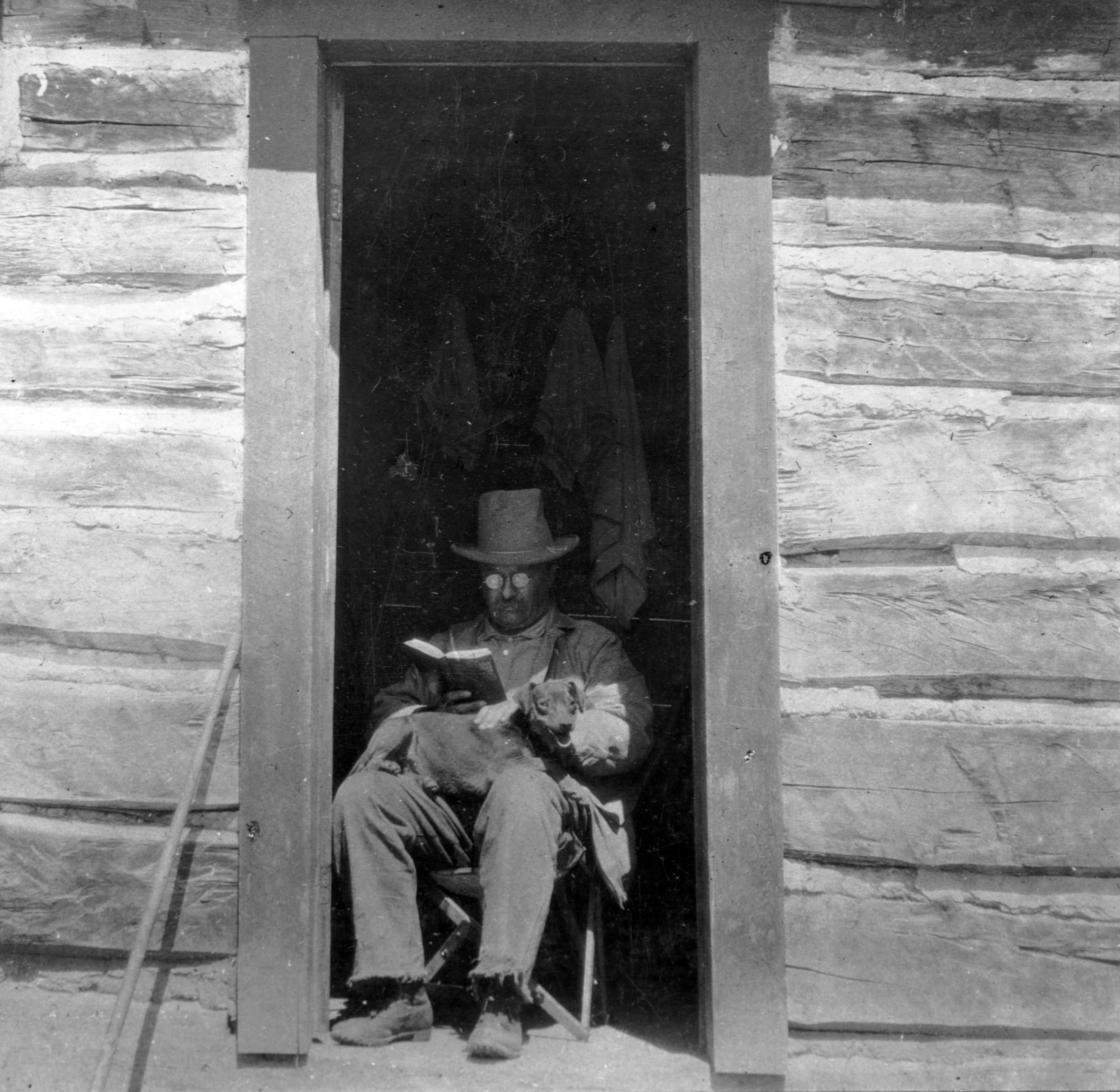Theodore Roosevelt in the doorway of his West Divide Creek Ranch house reading a book, 1905. (Credit: Alex Lambert/Library of Congress/Corbis/VCG/Getty Images)