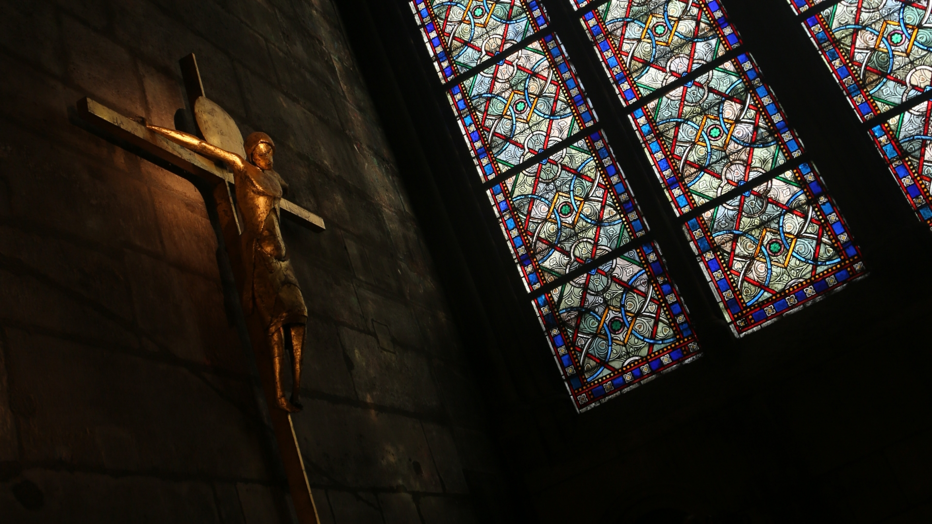Statue of Jesus Christ on the crucifix by a stained glass window inside Notre-Dame Cathedral, Paris. (Credit: Waring Abbott/Getty Images)