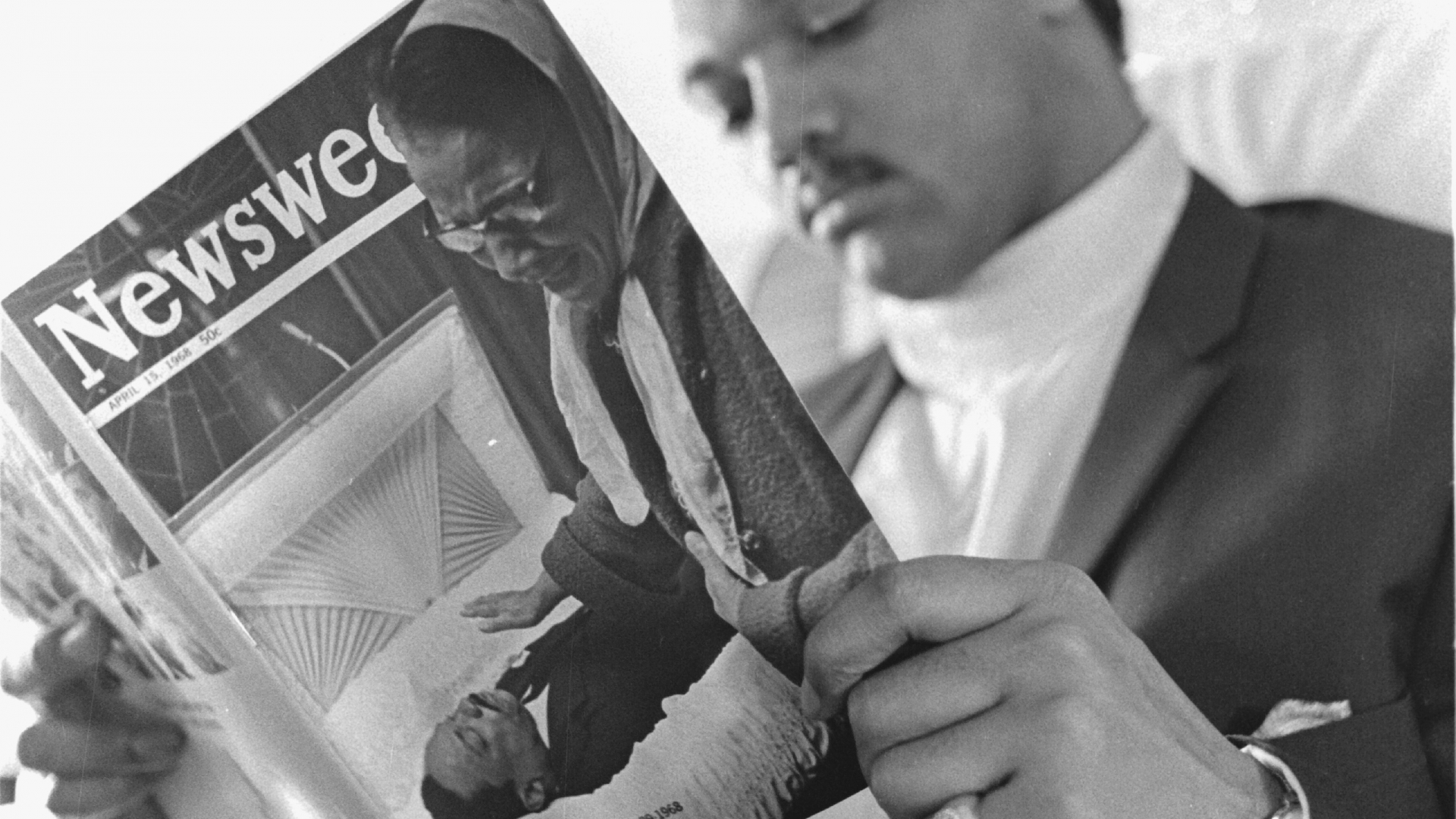 Jesse Jackson takes a moment to read a copy of Newsweek magazine, with a cover showing a mourner passing by the body of the recently assassinated Dr. Martin Luther King, Jr., during his flight from Atlanta to Memphis to carry out the Final March, 1968. (Credit: Robert Abbott Sengstacke/Getty Images)