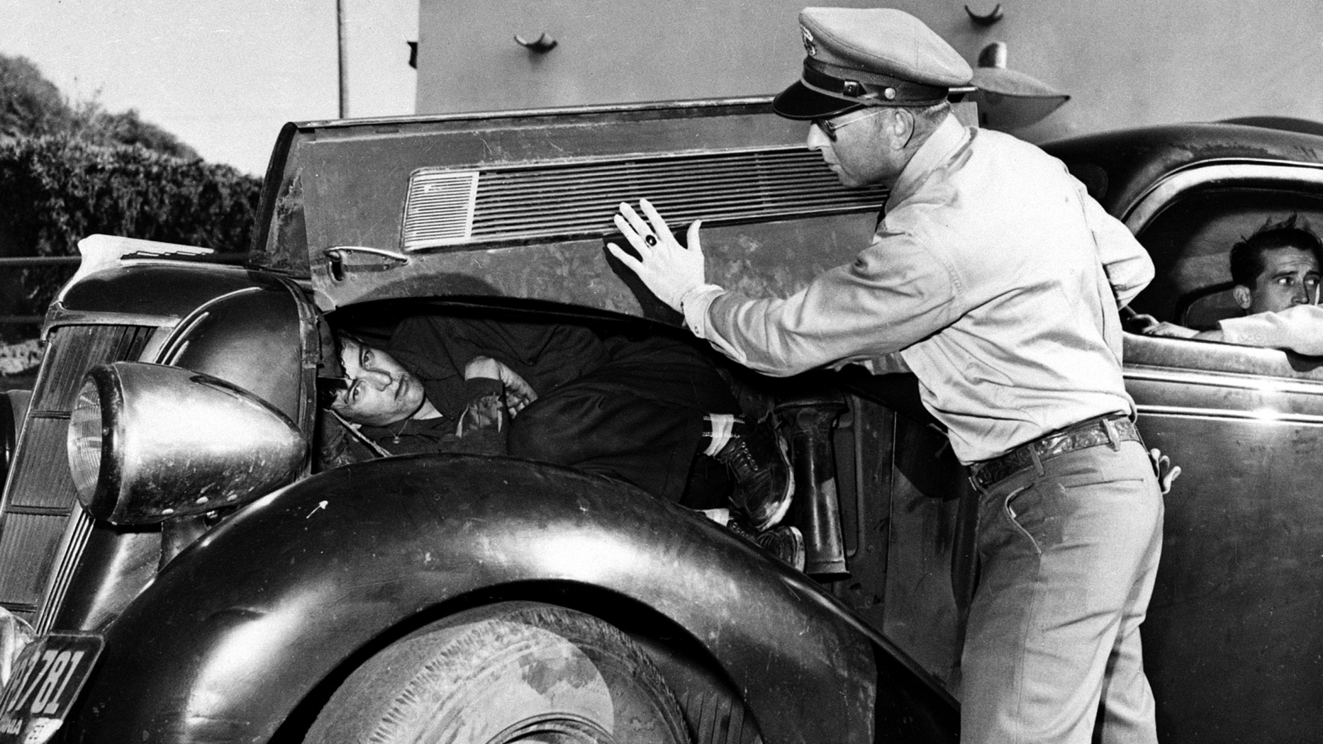 U.S. Border Patrol officer Richard McCown shows how he found Felipe Ramirez Perez, a 6-foot illegal Mexican immigrant, curled up on the engine beneath the hood of this automobile, at the U.S.-Mexican border at San Diego, Calif., March 15, 1954. Perez is held for illegal entry, awaiting deportation, and Felix Mercado Gutierrez, the driver of the car, is charged with attempt to smuggle Perez into the United States. (AP Photo)