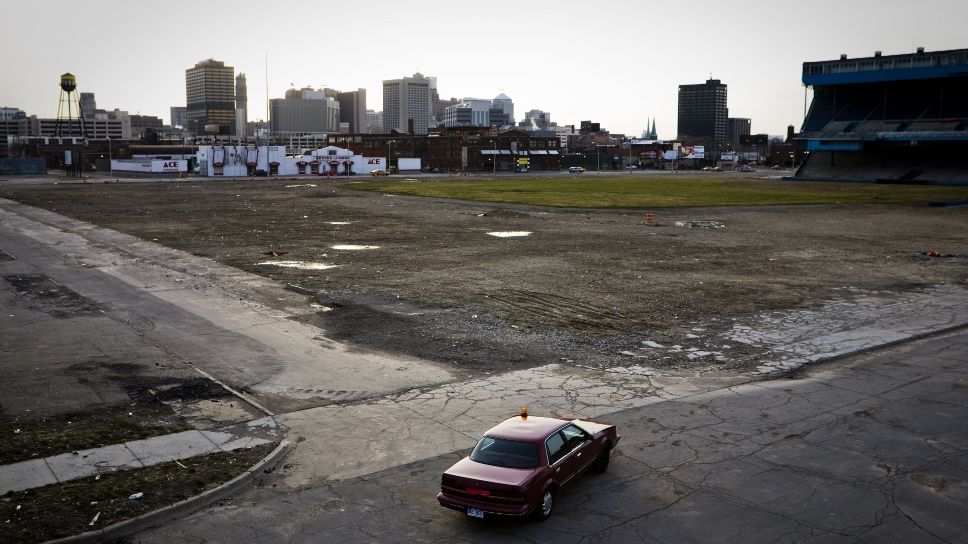 The historic Tiger Stadium baseball field sits in a slow state of decay near the remaining highrise buildings of downtown Detroit. For a rapidly growing population of urban pioneers, the crumbling landscape of Motor City is serving as a stage for experimentation and careful development of a new American Dream. (Credit: William Widmer/Redux)