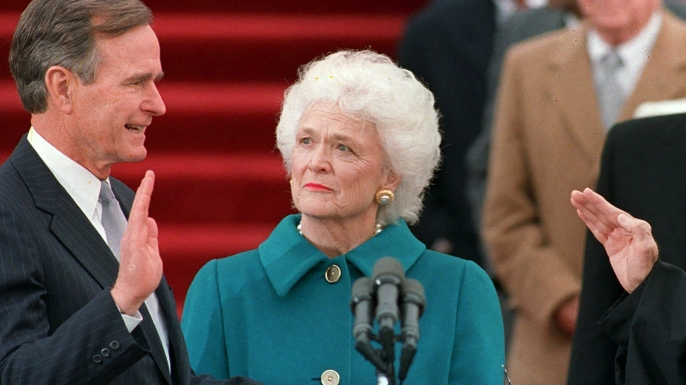 First Lady Barbara Bush holds the bible for her husband, George H.W. Bush, as he is sworn into office as the 41st president of the United States, 1989.  (Credit: Bob Daugherty/AP Photo)